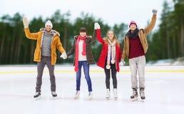 Amis heureux ondulant des mains sur la piste de patinage extérieure Images stock