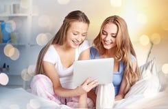 Amis heureux ou filles de l'adolescence avec le PC de comprimé à la maison Images libres de droits