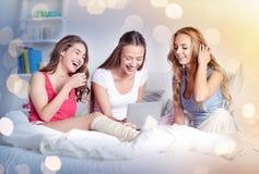 Amis heureux ou filles de l'adolescence avec le PC de comprimé à la maison Photographie stock
