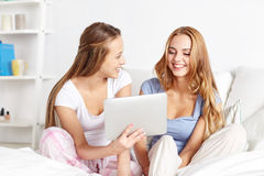 Amis heureux ou filles de l'adolescence avec le PC de comprimé à la maison Photos libres de droits