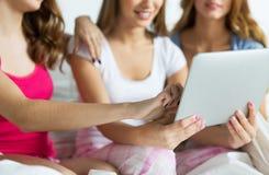 Amis heureux ou filles de l'adolescence avec le PC de comprimé à la maison Photo libre de droits