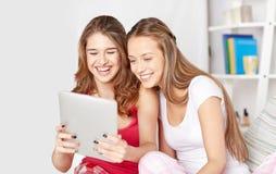 Amis heureux ou filles de l'adolescence avec le PC de comprimé à la maison Photos stock