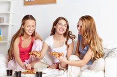 Amis heureux ou filles de l'adolescence mangeant de la pizza à la maison Images libres de droits