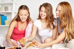 Amis heureux ou filles de l'adolescence mangeant de la pizza à la maison Photos stock