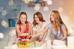 Amis heureux ou filles de l'adolescence mangeant des bonbons à la maison Photos libres de droits