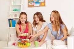 Amis heureux ou filles de l'adolescence mangeant des bonbons à la maison Image stock