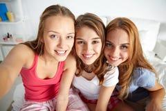 Amis heureux ou filles de l'adolescence prenant le selfie à la maison Image libre de droits