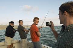 Amis heureux pêchant sur le yacht Photographie stock