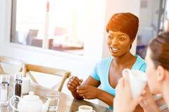 Amis heureux parlant et buvant du café et du thé Photographie stock libre de droits