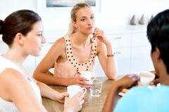 Amis heureux parlant et buvant du café et du thé Photo stock