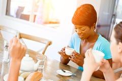 Amis heureux parlant et buvant du café et du thé Images stock