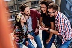 Amis heureux parlant et se tenant sur des étapes Photographie stock libre de droits