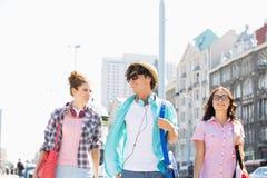 Amis heureux parlant tout en marchant dans la ville Photo libre de droits