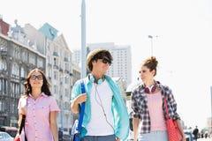 Amis heureux parlant tout en marchant dans la ville Photos libres de droits