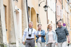 Amis heureux parlant tout en marchant dans la ville Image libre de droits