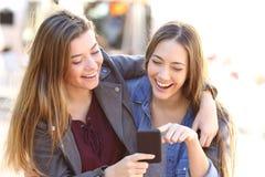 Amis heureux partageant un téléphone intelligent Images stock