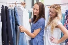 Amis heureux passant en revue dans le support de vêtements Photos stock
