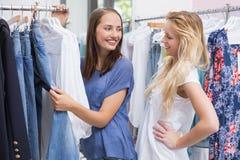 Amis heureux passant en revue dans le support de vêtements Images libres de droits