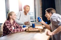 Amis heureux passant le temps ainsi que des boissons de pizza et de soude Images stock