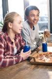 Amis heureux passant le temps ainsi que des boissons de pizza et de soude Image stock