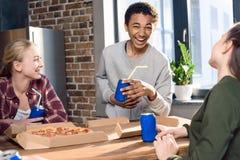 Amis heureux passant le temps ainsi que des boissons de pizza et de soude Image libre de droits