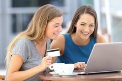 Amis heureux payant sur la ligne dans une barre Photos libres de droits