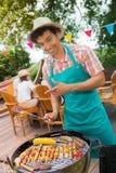 Amis heureux pendant un barbecue au BBQ de jardin de famille Photos libres de droits