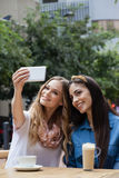 Amis heureux photographiant tout en se reposant au café de trottoir Image libre de droits