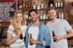 Amis heureux posant avec des bouteilles à bière au bar Photos stock
