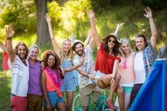 Amis heureux posant ensemble au terrain de camping Images libres de droits
