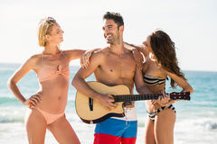 Amis heureux posant et jouant la guitare sur la plage Photo stock