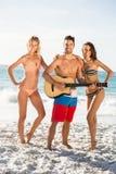Amis heureux posant et jouant la guitare sur la plage Photographie stock