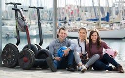 Amis heureux posant près des segways sur le rivage Photos libres de droits