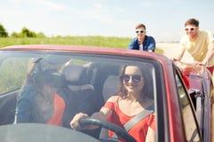 Amis heureux poussant la voiture cassée de cabriolet Photos stock