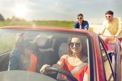 Amis heureux poussant la voiture cassée de cabriolet Images libres de droits