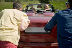 Amis heureux poussant la voiture cassée de cabriolet Images stock