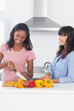 Amis heureux préparant des poivrons pour le repas Photographie stock