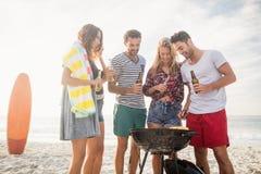 Amis heureux préparant le barbecue Photo stock