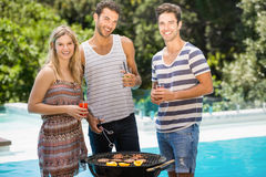 Amis heureux préparant le barbecue près de la piscine Photos libres de droits