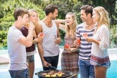 Amis heureux préparant le barbecue près de la piscine Photographie stock