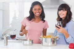 Amis heureux préparant le dîner ensemble Photos stock