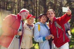 Amis heureux prenant des photos tout en augmentant Photo stock