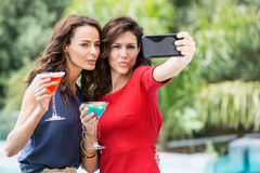 Amis heureux prenant l'autoportrait tout en se tenant boit Image libre de droits