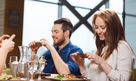Amis heureux prenant la photo de la nourriture au restaurant Photos libres de droits