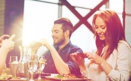 Amis heureux prenant la photo de la nourriture au restaurant Images stock