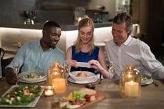 Amis heureux prenant la photo du repas avec le téléphone portable Photographie stock