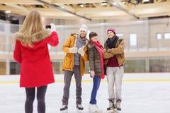 Amis heureux prenant la photo sur la piste de patinage Image stock