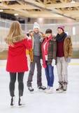 Amis heureux prenant la photo sur la piste de patinage Image libre de droits