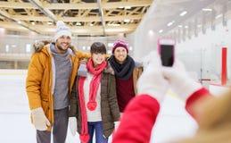 Amis heureux prenant la photo sur la piste de patinage Photographie stock libre de droits