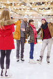 Amis heureux prenant la photo sur la piste de patinage Photo stock